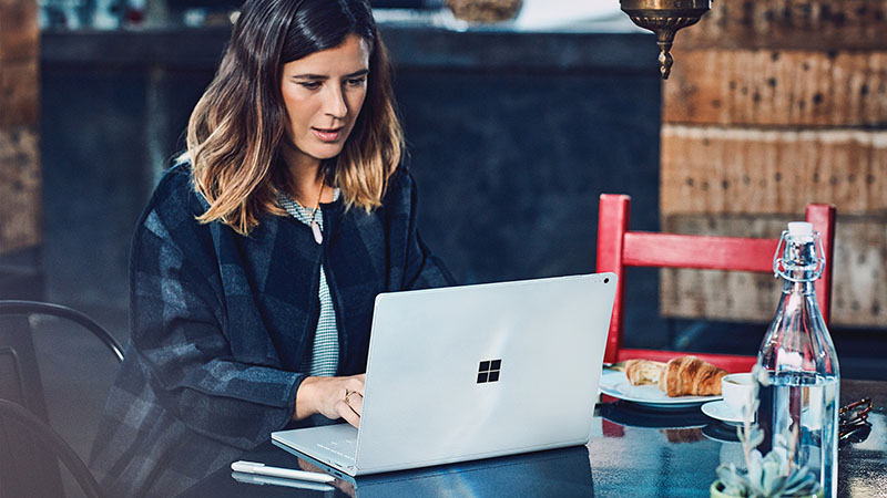 Woman sitting at cafe table with Surface